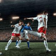 football players kicking ball