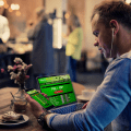 man trading on laptop and phone